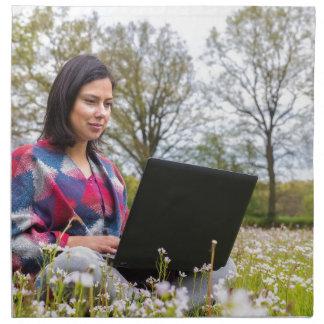 女性は咲く草原のラップトップによって坐ります ナプキンクロス