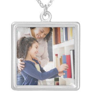 娘を救済している母は棚の本を選びます シルバープレートネックレス