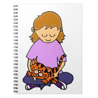 子ネコを握っているかわいい小さな女の子 ノートブック