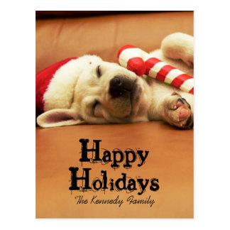 子犬はクリスマスのおもちゃが付いているソファーで眠ります ポストカード