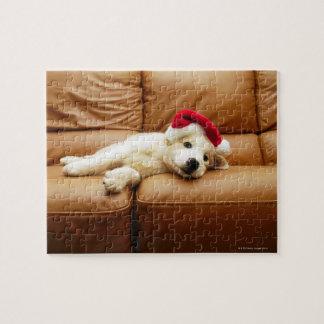 子犬はソファーにクリスマスの帽子そしてあることを身に着けています ジグソーパズル