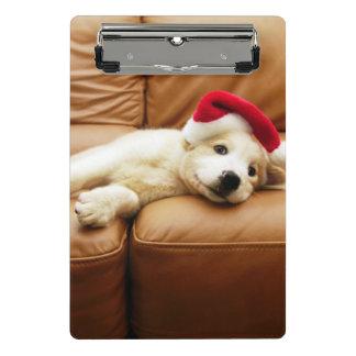子犬はソファーにクリスマスの帽子そしてあることを身に着けています ミニクリップボード