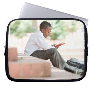 学校の外のステップの男の子の読書、 ラップトップスリーブ