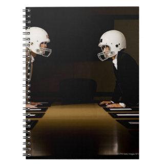 対決の身に着けているフットボールの女性実業家 ノートブック