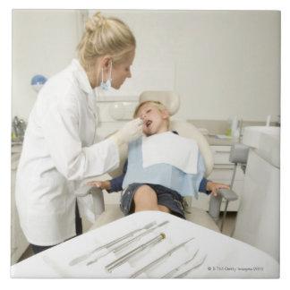 小さい男の子を検査しているメスの歯科医 タイル