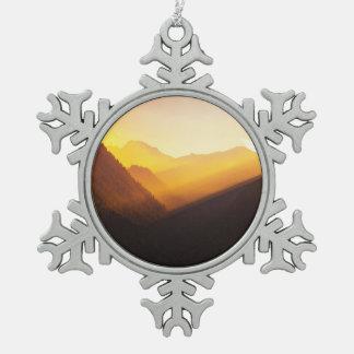 山は日没の美しい自然のシルエットを描きます スノーフレークピューターオーナメント