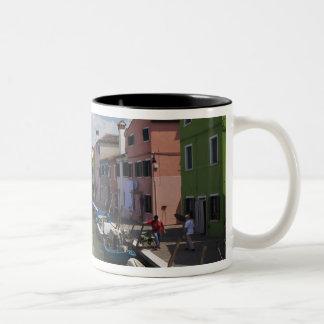 島の運河に沿うカラフルな家の ツートーンマグカップ