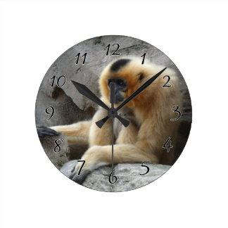 崖でリラックスしているオレンジおよび黒いテナガザルの写真 ラウンド壁時計