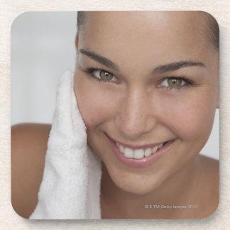 布が付いている彼女の顔をごしごし洗っている女性 コースター