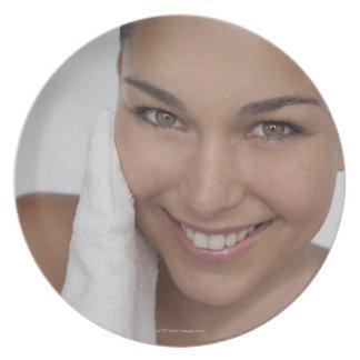 布が付いている彼女の顔をごしごし洗っている女性 プレート