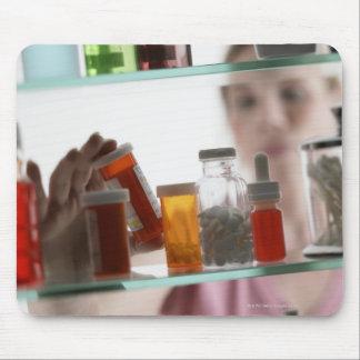 常備薬戸棚からの丸薬を取っている女性 マウスパッド