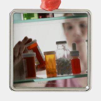 常備薬戸棚からの丸薬を取っている女性 メタルオーナメント