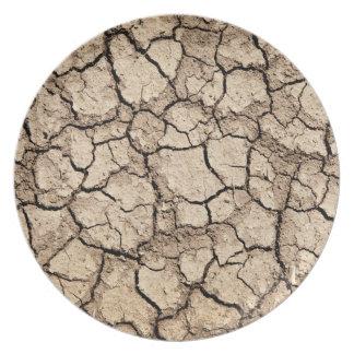 干ばつの間の乾燥した割れた地面 プレート