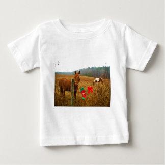 弓およびストッキングを持つクリスマスの馬 ベビーTシャツ
