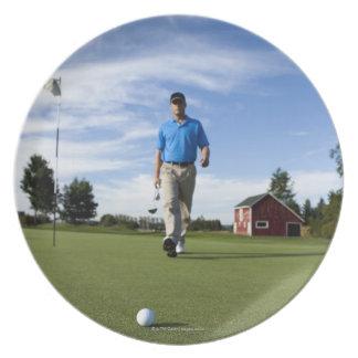 彼のゴルフ・ボールの方の人の歩く プレート