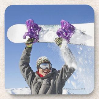 彼の頭部の上の彼のスノーボードを握っている若者 コースター