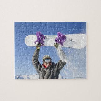 彼の頭部の上の彼のスノーボードを握っている若者 ジグソーパズル