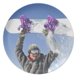 彼の頭部の上の彼のスノーボードを握っている若者 プレート