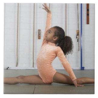 彼女の床を練習している若い女の子の体育専門家 タイル
