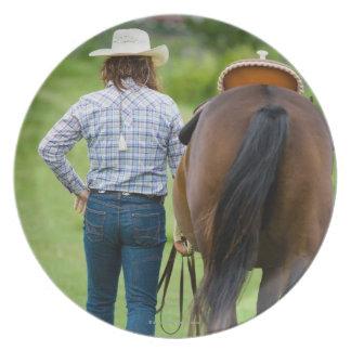 彼女の馬を導く女性の背部意見 パーティー皿