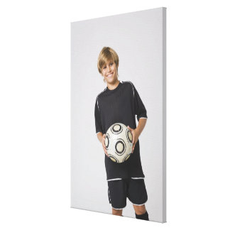 微笑するサッカーボールポートレートを握っている男の子 キャンバスプリント