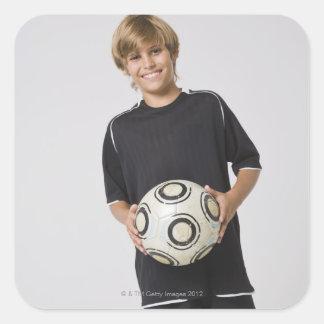 微笑するサッカーボールポートレートを握っている男の子 スクエアシール
