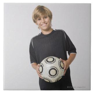 微笑するサッカーボールポートレートを握っている男の子 タイル