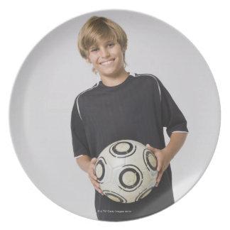 微笑するサッカーボールポートレートを握っている男の子 プレート
