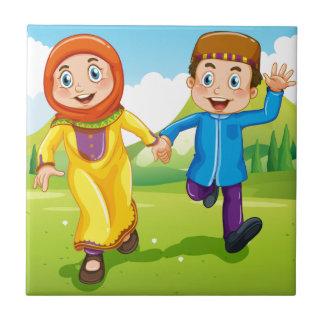 手を握っているイスラム教の男の子および女の子 タイル