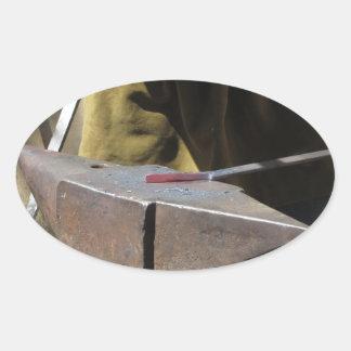 手動で溶解した金属を造っている鍛治屋 楕円形シール