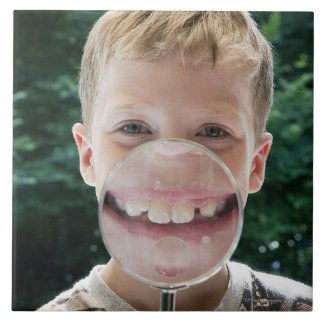拡大鏡の微笑の後ろのブロンドの男の子 タイル