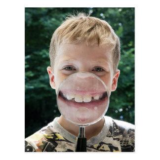 拡大鏡の微笑の後ろのブロンドの男の子 ポストカード