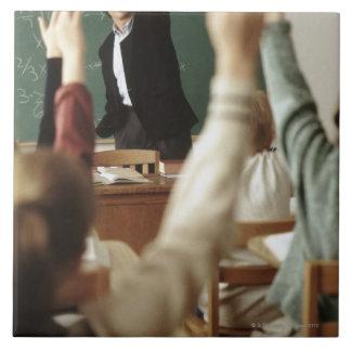 教室の彼らの手を上げている学生 タイル
