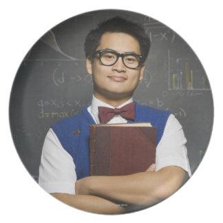 教科書を握っている真面目なアジア男子学生 プレート