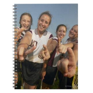 数に信号を送っている十代の(16-17の)ラクロスのチーム ノートブック