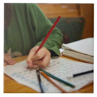 数学の宿題に集中している男の子 タイル