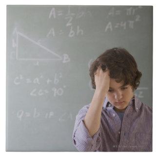 数学の黒板の前の十代の男の子 タイル