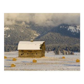 新しい雪2の後の素朴な納屋および干し草ベール ポストカード