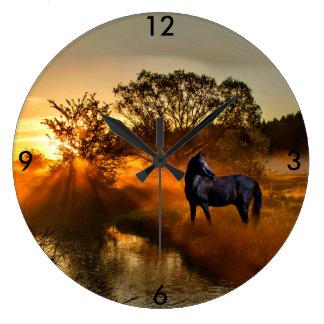 日の出または日没の黒い馬 壁時計