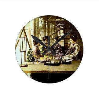 日本古い夕食で一緒に食事しているヴィンテージの芸者 ラウンド壁時計