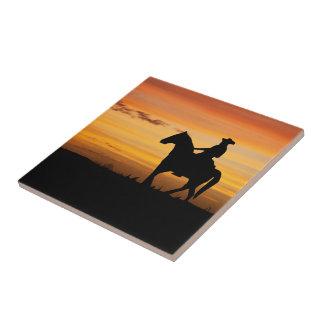 日没のカウボーイまたは女性のカーボーイの乗馬馬 タイル