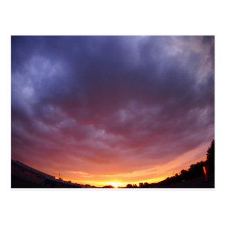 日没の前の都市上の雲が付いている空 ポストカード