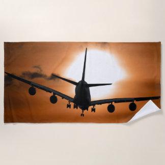 日没の空のジェット機の定期旅客機のシルエット ビーチタオル