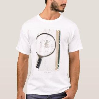 昆虫を示す本上の拡大鏡 Tシャツ