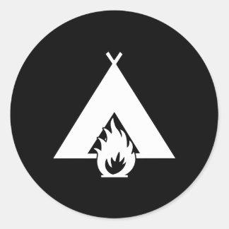 暗い背景のための白いキャンプファイヤーおよびテントの記号 ラウンドシール