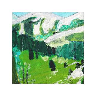 木々の緑に覆われた谷の雪によっておおわれる山 キャンバスプリント