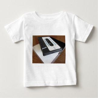 木のテーブルのヴィンテージのオーディオ・カセットテープテープ ベビーTシャツ