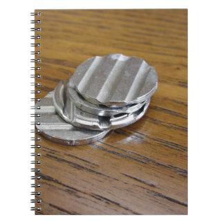 木のテーブルの空白のな金属硬貨 ノートブック