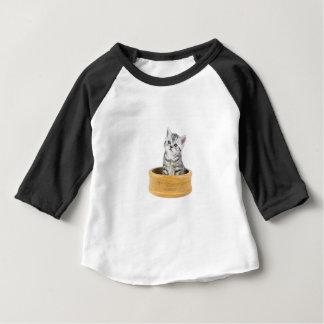 木ボールに坐っている若い銀製の虎猫猫 ベビーTシャツ