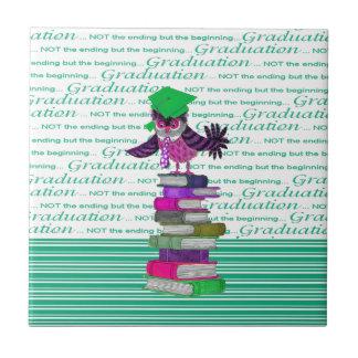 本の上のフクロウの身に着けているタイそして卒業生の帽子、卒業生 タイル
